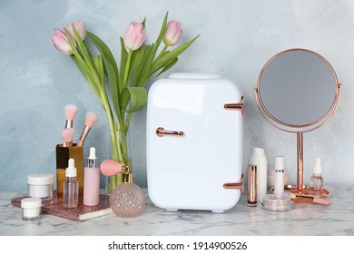 Cosmetic refrigerator and skin care products on white marble table