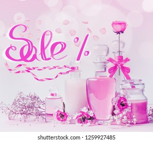 Cosmetic sale text lettering with glass product bottles , pink ribbons and flowers standing on white pink background with bokeh. Skin care, cosmetic shop, sale and abstract beauty concept. Neon color
