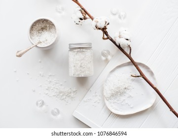 Cosmetic sea salt and cotton flowers on a white background