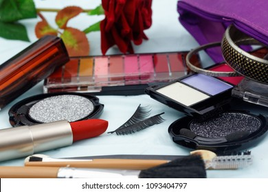 Cosmetic set with brushes and fake eye lashes with make up bag, artificial red rose and woman's accessory
