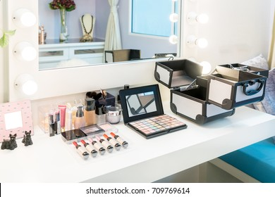 Cosmetic set with eye shadow, eye liner and powder on wood dressing table in home. Makeup brush and cosmetics for beauty.