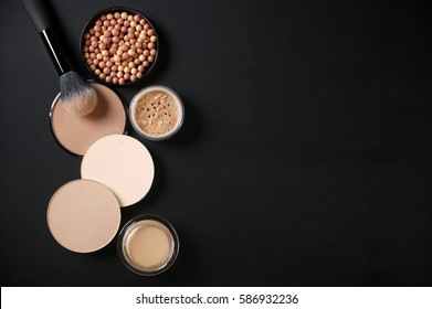 Cosmetic set of various shades compact and loose face powder, bronzed pearls, concealer and makeup brush on black background. Top view point, flat lay.