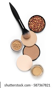 Cosmetic set of various shades compact and loose face powder, bronzed pearls and makeup brush isolated on white background. Top view point, flat lay.