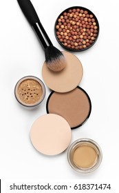 Cosmetic set of various shades compact and loose face powder, bronzed pearls and makeup brush on white background. Top view point, flat lay.