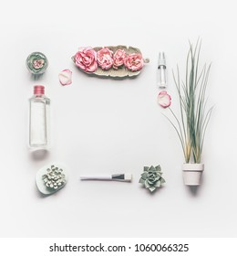 Cosmetic setting frame for facial skin care with pink roses and roses water or toner on white background, top view, place for text. Beauty and nature herbal cosmetic concept