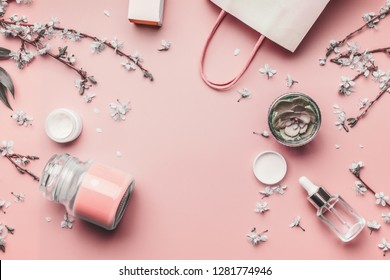 Cosmetic and skin care concept. Various facial products on pastel pink background with cherry blossom and leaves, top view, frame. Copy space for your design. Beauty blog and shopping layout. Flat lay