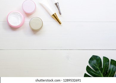cosmetic and skin care product and green leaves on white wood table, beauty with treatment cream and moisturizing on wooden desk, health and wellness concept, top view.
