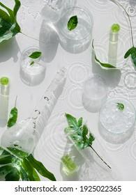 Kosmetischer Hautpflegehintergrund. Kräutermedizin mit grünen Blättern. Natürliches Sonnenlicht, lange Schatten. Wassertropfen, Spritzen. Chemische Glaswaren, Petrischalen, Durchstechflaschen. Natürlicher Hautpflegehintergrund.