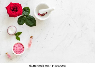 Cosmetic spa set with rose flowers and cream for body on white marble desk background top view mockup