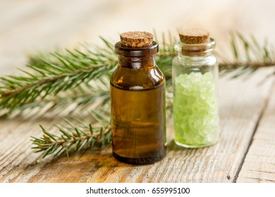 cosmetic spruce oil and salt in bottles with fur branches on wooden table background