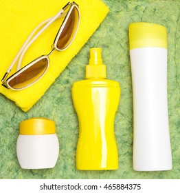 Cosmetic sunscreen products for face and body skin care, towel and sunglasses. Lotion, spray and cream. Cosmetics containing sun protection factor