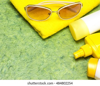Cosmetic sunscreen products for face and body skin care, towel and sunglasses. Lotion, spray and cream. Cosmetics containing sun protection factor. Copy space