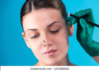 Cosmetic surgeon examining female client in office. Doctor draws lines with a marker, the eyelid before plastic surgery, blepharoplasty. Surgeon or beautician hands touching woman face. Rhinoplasty