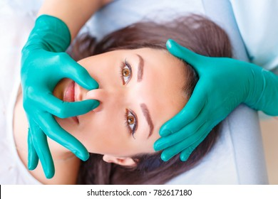 Cosmetic surgeon examining female client in office. Doctor checking woman's face, nose before plastic surgery. Surgeon or beautician hands touching woman face. Rhinoplasty