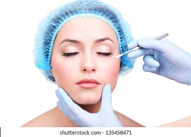 Cosmetic surgery with scalpel on young woman close up