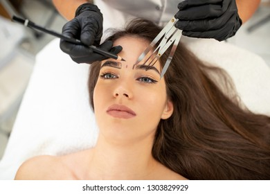 Cosmetic tattoo specialist using state of the art hand tools for enhancing eyebrows appearance