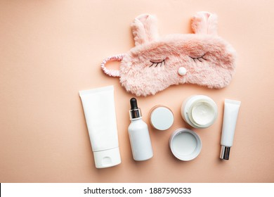 Cosmetic white containers with sleeping mask on pink background top view. Skin night care products. Hand, face, body moisturizing cream jar.