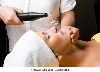 Cosmetician applying high frequency treatment to the face of a young beautiful woman in spa salon