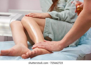 Cosmetician applying oil on skin. Healthy female legs. Body care tips.