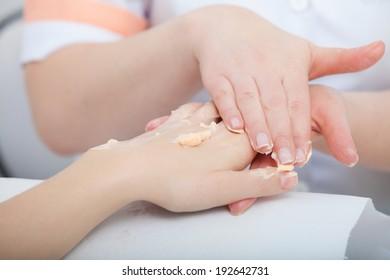 Cosmetician beautician applying orange moisturizing cream balm on hands of female client. Skincare. Woman in healthy beauty spa salon.