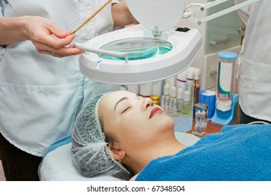 The cosmetician does face care procedure for the young woman