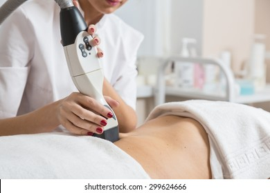 Cosmetician  making procedure of lymphatic drainage with a professional equipment