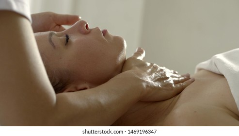 cosmetician is massaging face and decollete of adult woman lying on massage table in salon