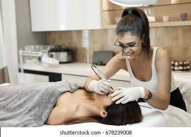 Cosmetician working at beauty-farm, making eyebrow tattoo.