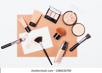 Cosmetics and accessories to create makeup in beige tones, arranged on white background, top view. Flat lay composition of decorative beauty products foundation, concealer, powder and brushes.
