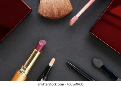 Cosmetics accessories on black cardboard background. Top view
