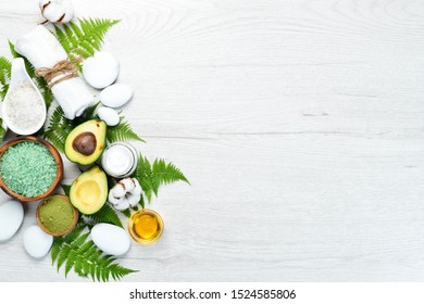 Cosmetics from avocado, avocado oil, sea salt and face cream, on a white wooden background. The concept of cosmetics and spa. Top view. Free copy space.