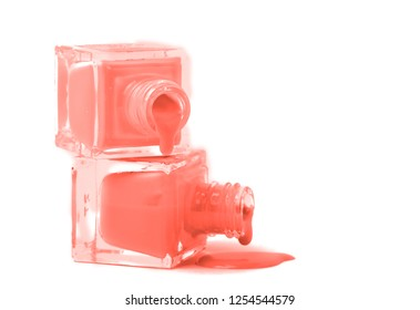 cosmetics and beauty image of a group of two Living Coral colored nail polish bottles on spilled paint isolated on white. Top view, flat lay. Free Copy space. Color of year 2019 concept. 16-1546