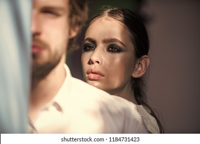 Cosmetics, beauty, visage concept. Man with beard in shirt. Woman look out behind man shoulder. Couple of fashion models. Girl with makeup face.