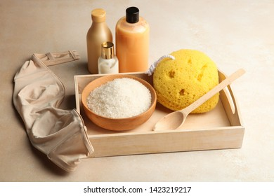 Cosmetics for body care, washcloth, brassiere and sea salt on wooden tray on neutral background. Concept bath, spa.
