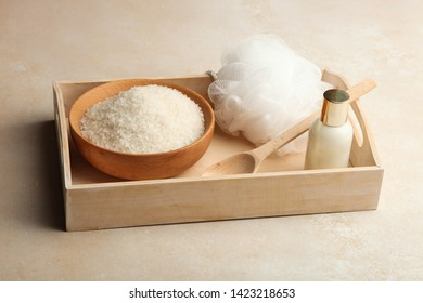 Cosmetics for body care, washcloth and sea salt on wooden tray on neutral background. Concept bath, spa.