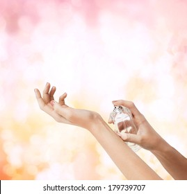 cosmetics, body parts and beauty concept - close up of woman hands spraying perfume