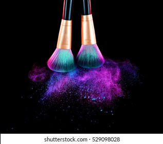 Cosmetics brush and explosion makeup dust powder background