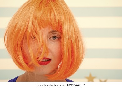 Cosmetics for care and revival. Lady red ginger wig and make up close up. Coloring and treatment professional salon service. Wig bright artificial hair looks unnatural. Hair revival procedure advice.