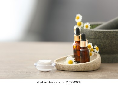 Cosmetics with chamomile extract on table