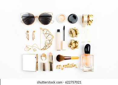 Cosmetics collage with lipstick, brush and other accessories on white background. Composition in gold colors. Flat lay, top view.