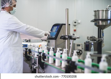 Cosmetics fabric worker typing on fabric production computer while liquid soap going on a production line.