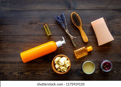 Cosmetics for hair care with jojoba, argan or coconut oil. Bottles and pieces of oil on dark wooden background top view.