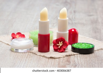 Cosmetics for lip skin care: sea salt, natural honey scrub with essential oils, lip cream and balms with flowers on shabby wooden surface and sackcloth napkin