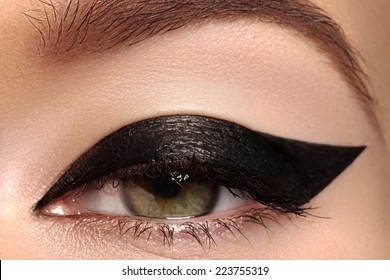 Cosmetics & make-up. Beautiful female eye with sexy black liner makeup. Fashion big arrow shape on woman's eyelid. Chic evening make-up