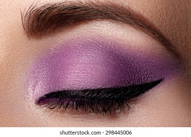Cosmetics & make-up. Beautiful female eye with sexy black liner and bright purple makeup. Fashion classic arrow shape on woman's eyelid. Chic evening make-up