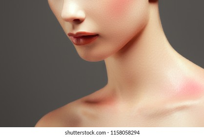 Cosmetics, makeup and beauty trends. Bright lip gloss and lipstick on lips. Closeup of beautiful female mouth with red lip makeup. Beautiful part of female face. Perfect clean skin