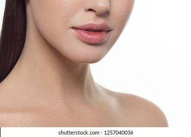 Cosmetics, makeup and trends. Bright lip gloss and lipstick on lips. Closeup of beautiful female mouth with natural lip makeup. Beautiful part of female face. Perfect clean skin in red light