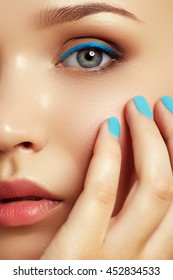 Cosmetics and makeup. Trendy colourful nails and makeup. Woman's face with vivid makeup and colorful nail polish. Portrait of fashion model with fashion makeup and mint manicure. Beauty female face