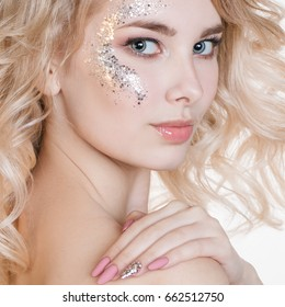 Cosmetics and manicure. Beauty women portrait of young curly blond woman with pastel manicure and perfect art make-up with glitter. Isolated