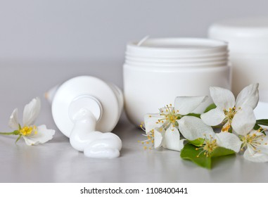 Cosmetics on a light background with spring flowers. Hand care cream comes out of the tube, in white jars there are cosmetic products for face and body care. Spring make-up. Still life